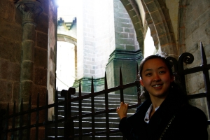 Shen Yun dancer Jade Zhan at the entrance to the St. Michel abbey and cathedral (Annie Li).