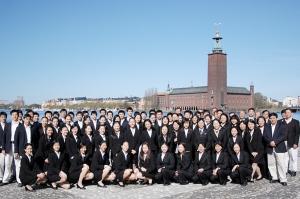 La Touring Company prend la pose pour une photo de groupe devant le port et l'hôtel de ville de Stockholm.