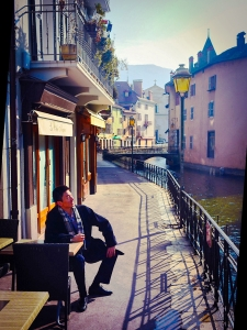 """Here, Principal Dancer and fellow blogger Ben Chen enjoys the morning sun along the Thiou Canal. You can see why the Thiou is considered the postcard of Annecy, hence the town's nickname """"Venice of the Alps."""" Lake Annecy is France's third largest lake. It was formed some 18,000 years ago and is fed by many small rivers from the surrounding mountains. Lake Annecy is known as Europe's cleanest lake because of strict environmental regulations introduced in the 1960s. (Ben Chen's Apple device)"""