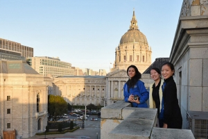 Left to right: Erin Battrick, Emily Pan, Michelle Wu with San Francisco's City Hall in the background on the balcony of the War Memorial Opera House.