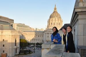 Från vänster till höger: Erin Battrick, Emily Pan och Michelle Wu med San Franciscos City Hall i bakgrunden på balkongen av War Memorial Opera House.