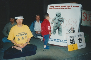Day one of a hunger strike in front of the Embassy of the People's Republic of China in London, 2001. Ben Chen's mother is on hunger strike, front left, as a toddler looks at a picture of a baby who was killed as a result of the persecution of Falun Gong in China.