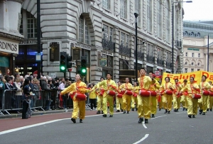 London New Year Parade, Ben Chen at front right and other Falun Gong practitioners play waist drums along with hundreds of other groups parading down Piccadilly.