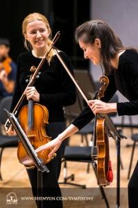 수석 바이올린 연주자 폴리나 마주르키에브이치와 바이올린 연주자 엘리자베스 레이놀즈가 함께 웃고 있다.