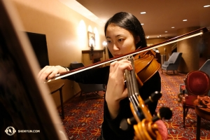 Violinist Karen Chen in focused preparation. Performers like Ms. Chen — even as she closes in on 100 performances this year alone and with 11 such Shen Yun seasons under her belt — are always striving to further perfect their art. (Photo by Annie Li)