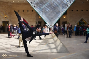After waiting in the long line for tickets, dancer Zack Chan decided to feel the power of the Louvre pyramid. (Photo by dancer Jun Liang)