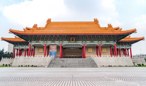 The full grandeur of Taiwan's National Concert Hall with its golden roof, upturned eaves, and massive red colonnades, reminiscent of the palaces of the Ming and Qing Dynasties of China (1368–1912).