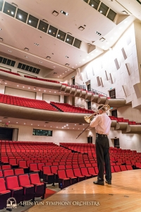 Trombonist Alistair Crawford warms up before a soon to be full concert hall.