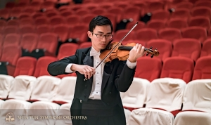Violinist Ian Zhong warms up before the concert.