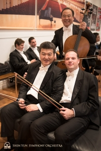 Principal bassist Juraj Kukan (R) and bassist Wei Liu wait to be reunited with their instruments on stage—cellist James Zheng doesn't need to wait.