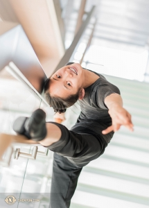 Angelia Wang, uit Chicago, gebruikt de leuning van de glazen trap van het theater als een barre voor haar warming-up!