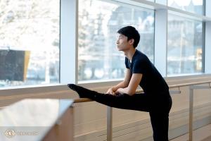Tanečník Tim Lin sleduje vnějšek zpoza jednoho z mnoha velkých skleněných oken Four Seasons Centre.