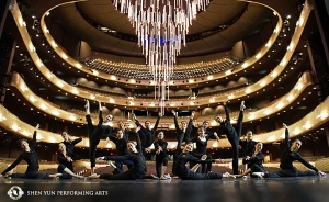 The Shen Yun World Company poses in the Winspear Opera House in Dallas, Texas. The theater was designed as a 21st-century version of a traditional opera house. The theater's enormous retractable chandelier hangs in the background.