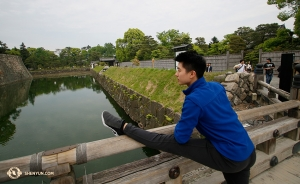 Principal Dancer Roy Chen multitasks, appreciating one of the moats at Nijo Castle while stretching! (Photo by dancer Nick Zhao)