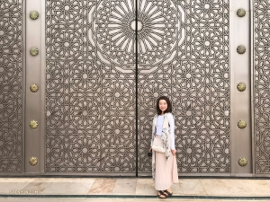 Here she stands in front of an intricately carved set of doors.