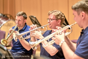 Principal trumpeter Eric Robins (L) works with his section.