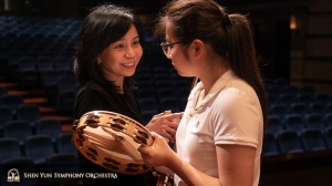 Concertmaster Chia-Chi Lin sharing a tip with percussionist Jazmine Jia.