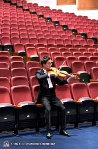 Il violista Jeff Lai si riscalda tra le poltrone della platea al Zhongli Arts Hall di Taoyuan