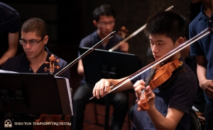 Violinists and stand buddies Gustavo Briceño and Zhengnian Song prepare for rehearsal.