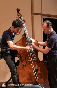 Double bassist TK Kuo (L) and Principal Double Bassist Juraj Kukan inspect Kuo's bass.
