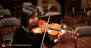 Concertmaster Chia-Chi Lin practices onstage before the show.
