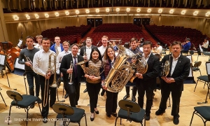 After a great tour, the brass section (plus one) gathers for a group photo—can you spot the non-brass musician?