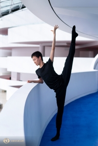Dancer Zhiheng Li peeks at the lower level as he warms up. (Photo by Kenji Kobayashi)