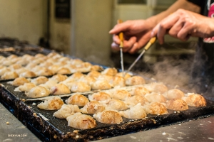 Takoyaki—Osaka's signature street food—octopus dumplings that are shaped and turned with steel pins while cooking.