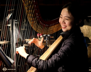 Harpist Crystal He warms up in the orchestra pit of the Ordway Center. (Photo by Karen Chen)