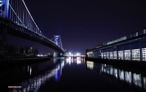 A night view of the Benjamin Franklin Bridge suspended over the Delaware River.