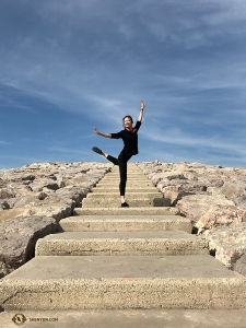 Dancer Daoyong Zheng poses on the stone steps near the beach. (Photo by projectionist Annie Li)