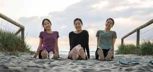 Dancers (from left) Liz Lu, Michelle Wu, and Daniella Wollensak get up early and enjoy some sand between their toes.