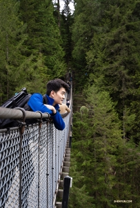 Built in 1889, Capilano Suspension Bridge stretches 450 feet (137m) across and 230 feet (70m) above Capilano River. Principal Dancer William Li enjoys the elevated view. (Photo by Sam Pu)