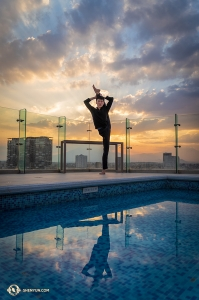 On the hotel's rooftop, dancer Edwin Fu balances by the pool. (Photo by William Li)