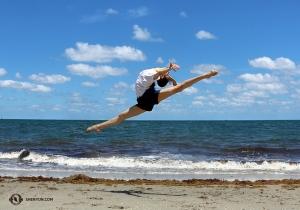 藍天、白雲、碧海、銀沙——舞蹈演員Carol Huang在海灘上高興地一躍而起——都快碰到天上的白雲了!