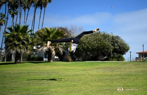 Taking advantage of the open space at Dana Point Harbor, Principal Dancer Elsie Shi performs a flip in the field. (Photo by Annie Li)