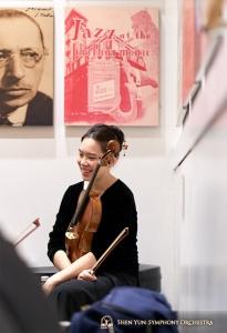 La violista Chani Tu davanti a un muro di manifesti storici.