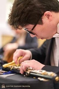 Pemain klarinet utama Yvegeniy Reznik sedang memeriksa instrumennya saat jeda istirahat.