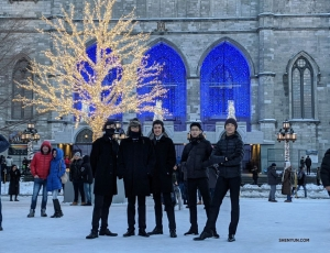 Dressed for the weather, dancers pose together in front of the well-known church located in the historic district of Old Montreal.