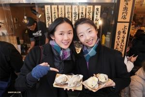 Les premières danseuses Angelia Wang (à gauche) et Melody Qin dégustent une spécialité locale de coquillages.