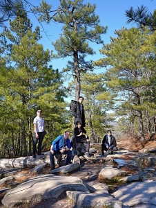 Dancer Jim Chen (top left), stage manager Lawrence Chang (left), and dancers Kenji Kobayashi (top center), Kelvin Diao (center), and Roy Chen (right) of Shen Yun New Era Company explore the natural surroundings of the park. (Photo by Fu TzuYuan)