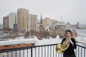 Meanwhile, on a record-breaking- snowfall weekend, french horn player Chi-Chien Weng from Shen Yun World Company warms up while cooling down in snowy Detroit, Michigan. (Photo by Grace Mo)