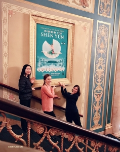 In the lobby of the timeless Detroit Opera House we have (from left) cellist Jasmine Jordan, violist Paulina Mazurkiewicz, and oboist Leen De Blauwe next to an exquisitely framed Shen Yun poster.