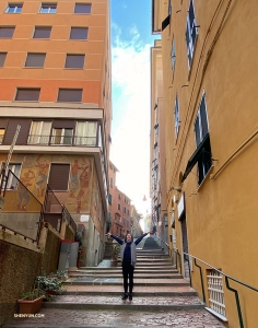 A dancer trekking up a steep alley in the city.