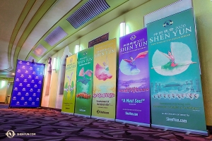 The performers are greeted by a rainbow of previous year's Shen Yun banners alongside this year's design, at the Eventim Apollo.