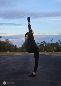 Dancer Jiajia Li steps off the bus and takes the opportunity to do some stretching in the parking lot (she didn't even warm up before doing this!).  (Photo by Kaidi Wu)