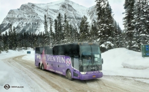 The group's vibrant Shen Yun tour bus adds a splash of color to the white snow and dark evergreens.