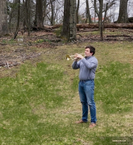 Trumpet player Eric Robins in his backyard. He says he's playing nature's melody.
