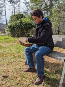Percussionist Brian Marple took his tambourine out for some fresh air in his yard. Yes, the trees and bench make his backyard look like a park.
